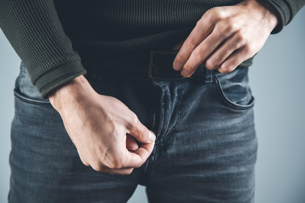 Man  hand chain in pants on gray background