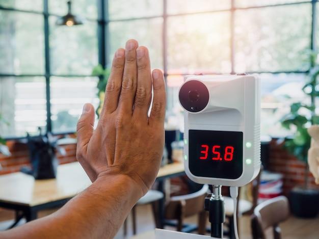 남자는 디지털 자동 체온 측정기로 카페에 들어가기 전에 온도를 확인합니다. 커피숍에 있는 디지털 온도계 기계 적외선 스캐너.