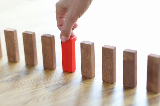 Man hand choosing red block among wooden closeup how to make right choice concept