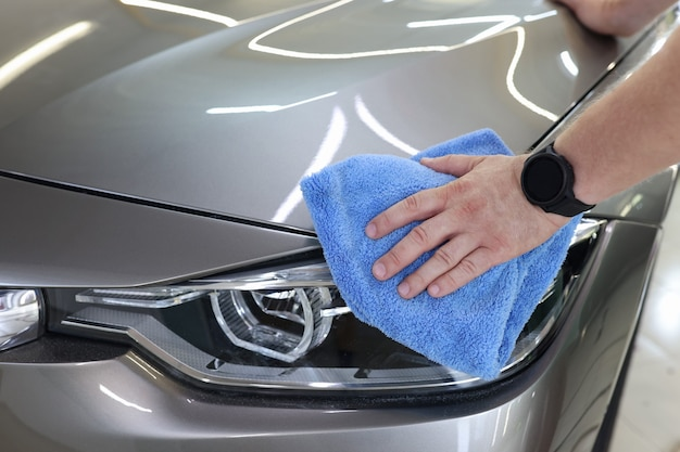 Man hand cleaning car and drying vehicle with microfiber cloth car detailing and car wash