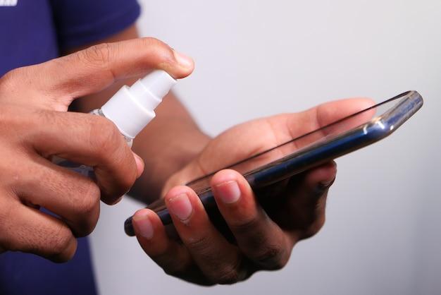 男の手が携帯電話のディスプレイをクリーニングします。
