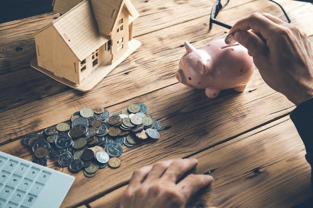 Человек вручает монеты с калькулятором и моделью дома на столе