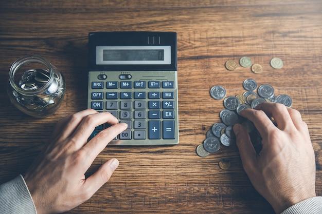 机の上の電卓で男の手コイン