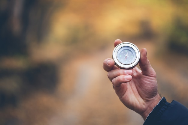 Man hand compass in autumn forest