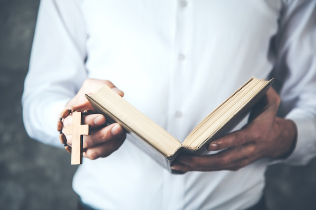 Man hand cross with book on dark background