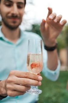남자 손 스파클링 와인 한 잔에 딸기를 드롭. 아름다운 삶, 셀레 브레이션