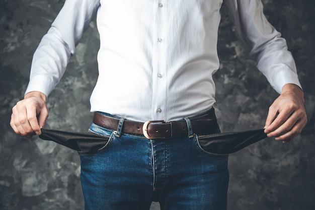 Man hand empty pocket on dark background