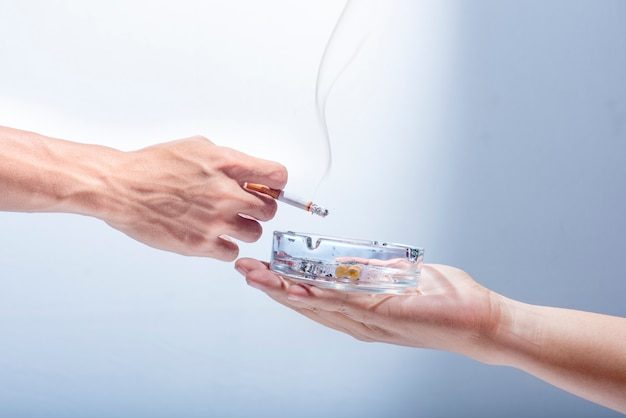 Man hand give a transparent ashtray to smoker