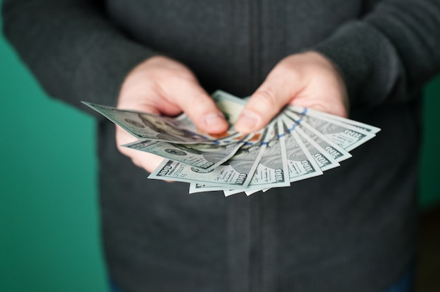 Man hand giving 100 dollar bills