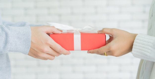 Man hand giving red gift box to woman