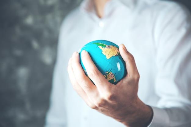 Man hand globe on dark background