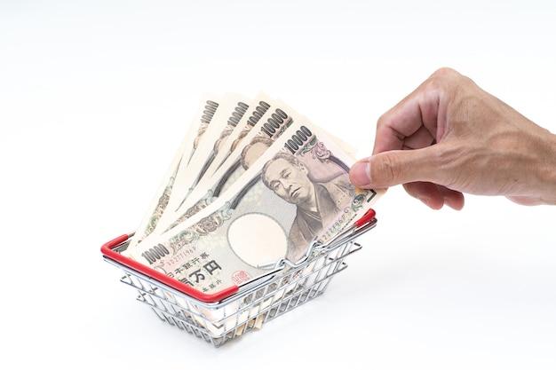 Man hand grabbing japanese banknote in shopping basket on white background