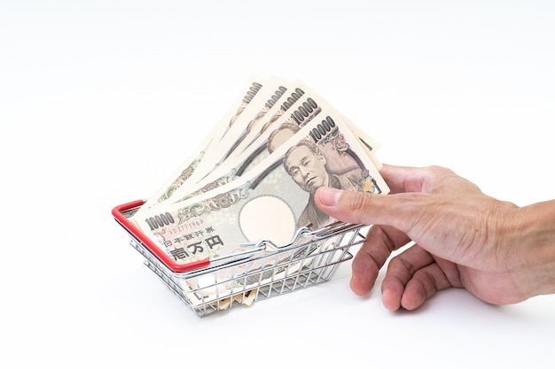 Man hand grabbing japanese banknote in shopping basket on white background