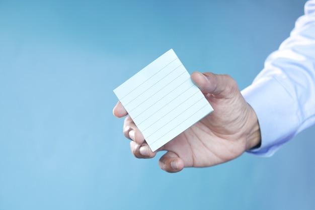 파란색 배경에 스티커 메모를 들고 있는 남자