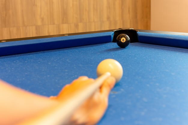 Man hand hold a billiard stick end the game.
