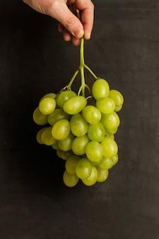 Рука человека, держащая гроздь зеленого винограда на темном фоне