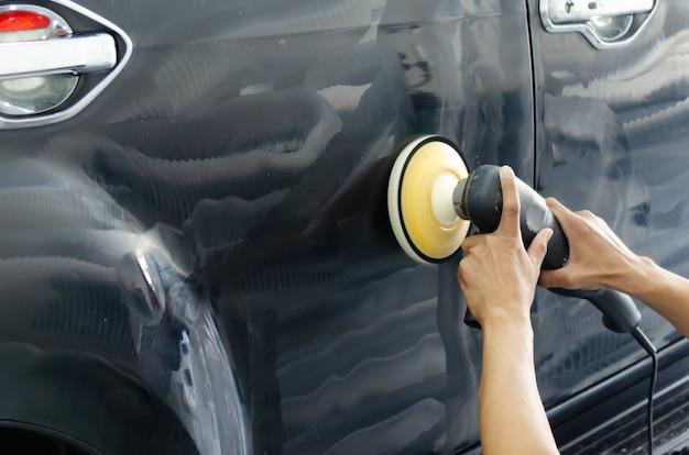 Рука человека, держащая машину для полировки автомобилей. детализация автомобиля полировка и воск.
