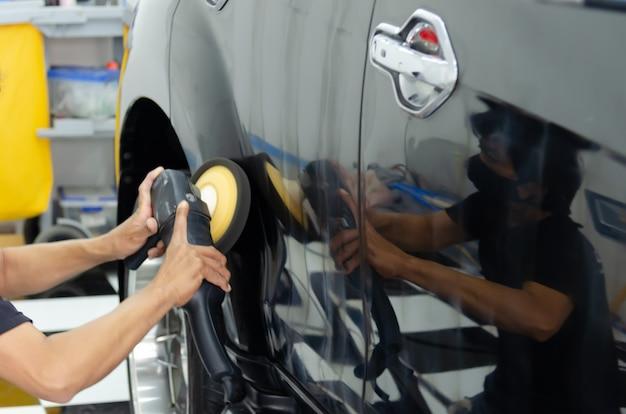 車の研磨機を持っている男の手。カーディテールバフとワックス。