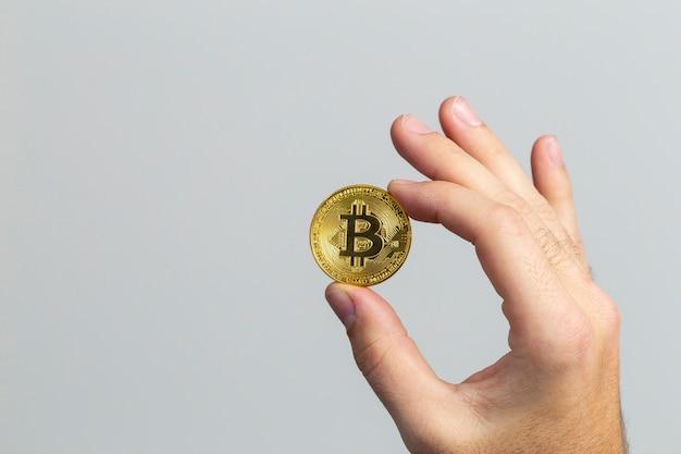 白い背景の前に物理的なビットコインを持っている男の手