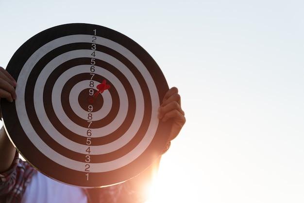 Укомплектуйте личным составом руку держа цель при дротики ударяя центр. концепция бизнес-цели.