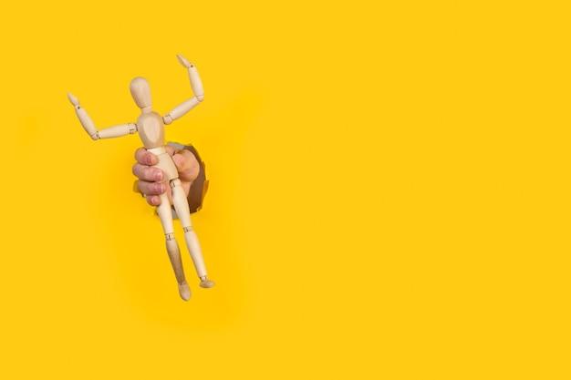Рука человека, держащая деревянную игрушку-манекен через отверстие в желтом
