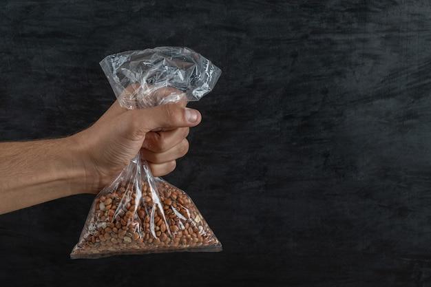 Mano dell'uomo che tiene una borsa con fagioli nani marroni crudi.