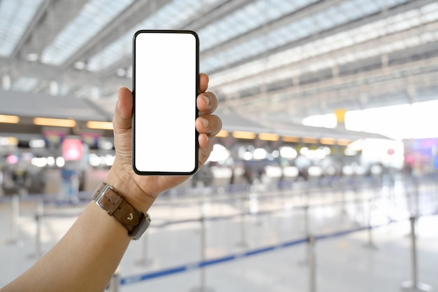 Man hand holding blank screen mobile smart phone in airport terminal counter background