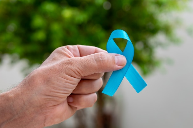 青いリボンを持っている男の手。青い11月。前立腺がん予防月間。男性の健康。