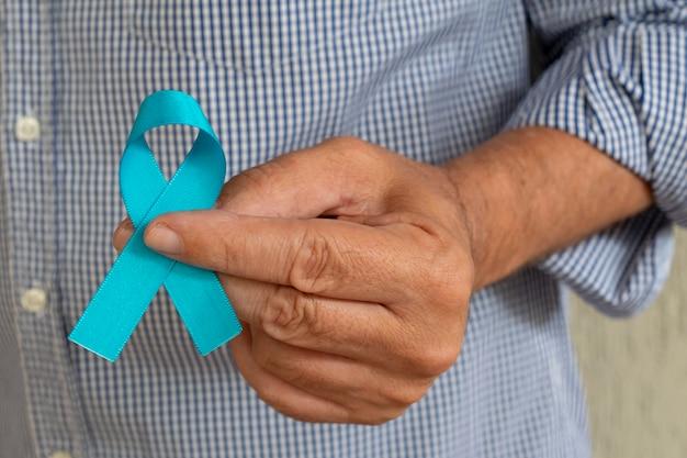 青いリボンを持っている男の手青い11月前立腺がん予防月間メンズ健康