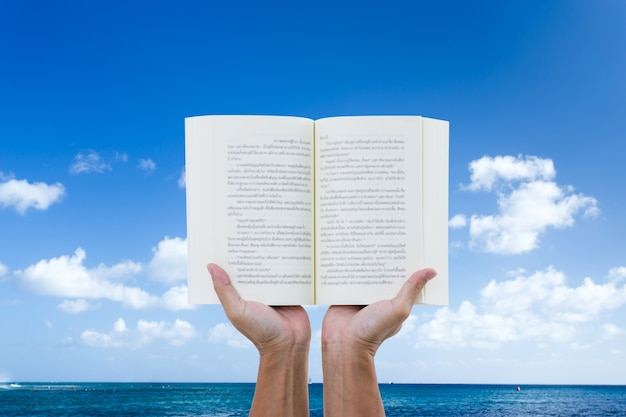 Man hand holding book with sea and blue sky background