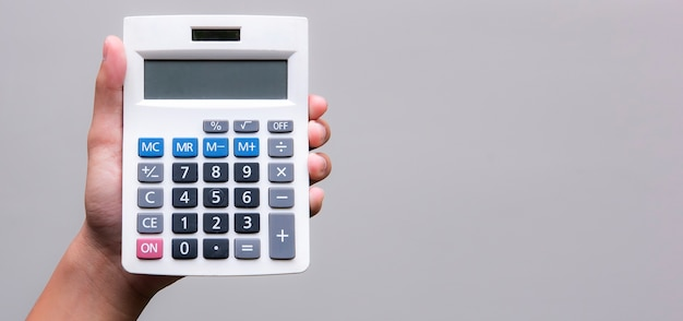 Man hand holding calculator  on gray background with copy space