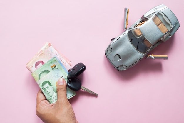 Man hand holding car key and thai banknotes with car model on pink background