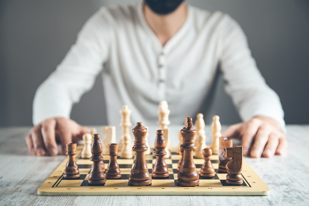Man hand holding chess on board
