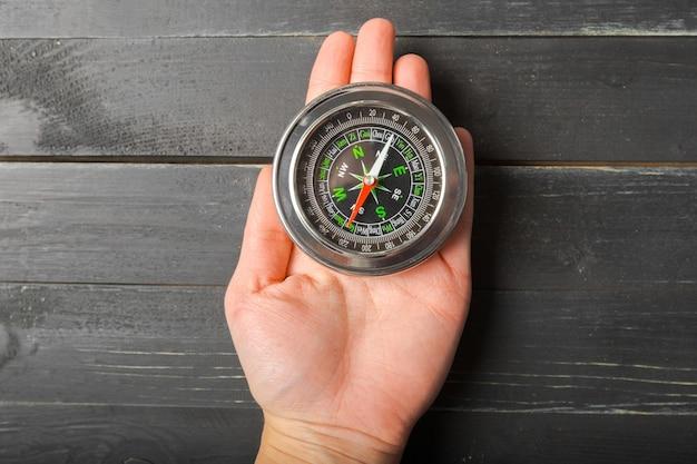 Man hand holding chrome compass