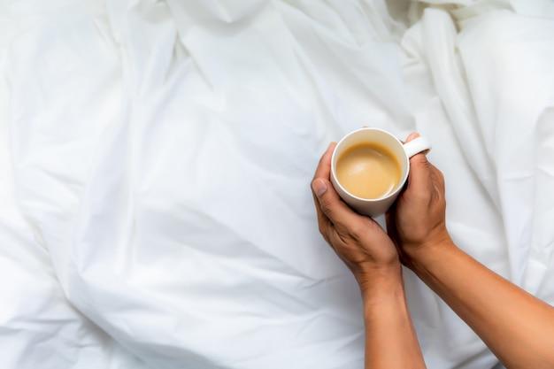 Рука человека с чашкой кофе на белой ткани вид сверху