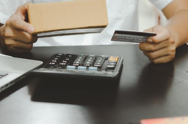 신용 카드와 소포 상자를 들고 남자 손입니다. 온라인 쇼핑 비즈니스 개념입니다.
