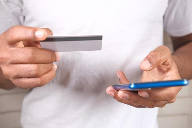 クレジットカードを持って、オンラインショッピングのスマートフォンを使用して男の手