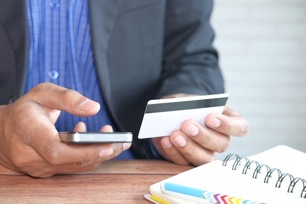 신용 카드를 들고 스마트 폰 온라인 쇼핑을 사용하는 사람 손