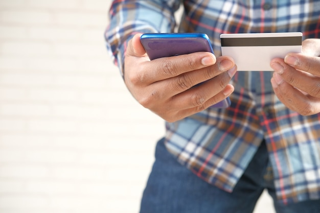 신용 카드를 들고 스마트 폰 온라인 쇼핑을 사용하는 사람 손.