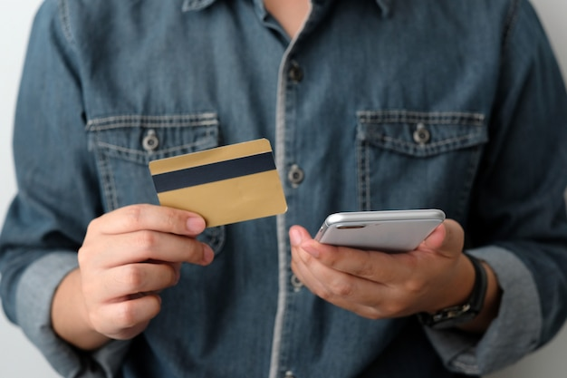 Man hand holding credit card and smartphone