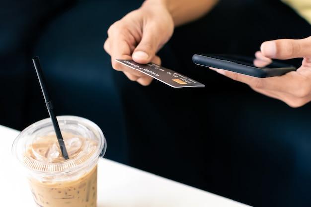 커피 카페에서 스마트폰으로 신용 카드를 들고 있는 남자 손.