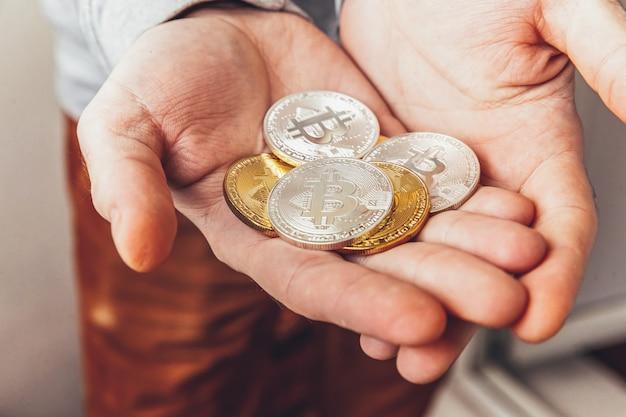 Человек рука держит криптовалюту золотую и серебряную монету биткойн