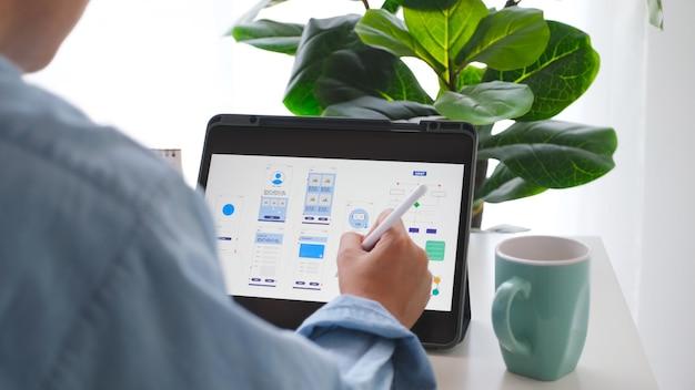 Рука человека, держащая цифровой планшет с прототипом разработки мобильных приложений, работая дома