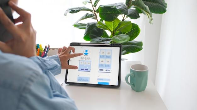 Рука человека, держащая цифровой планшет с разработкой мобильных приложений