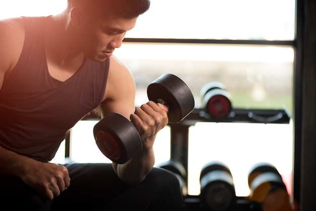 Man hand holding dumbbell exercise in gym. fitness muscular body exercise