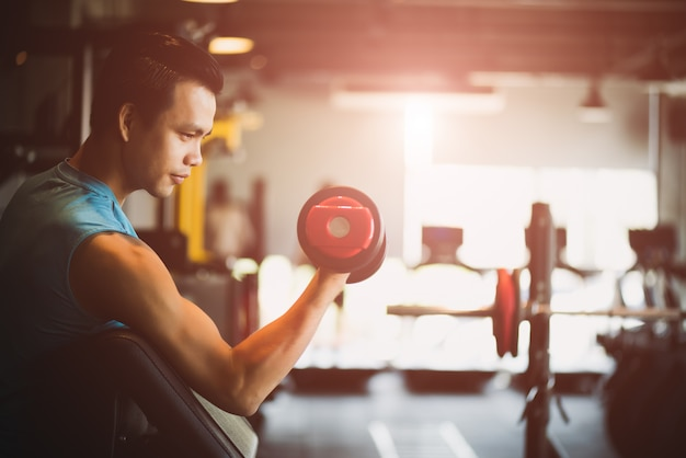 Man hand holding dumbbell exercise in gym