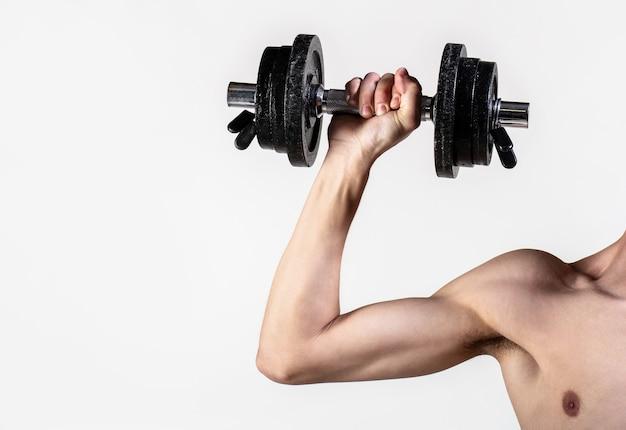 Человек рука гантели в руке. тощий парень держит в руках гантели. худой мужчина занимается спортом с гантелями. человек со слабой рукой поднимает тяжесть