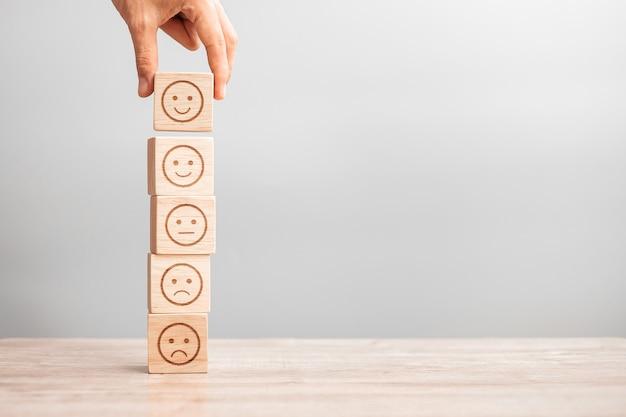 남자 손을 잡고 감정 얼굴 블록입니다. 고객은 사용자 리뷰를 위해 이모티콘을 선택합니다. 서비스 등급, 순위, 고객 리뷰, 만족도, 평가 및 피드백 개념