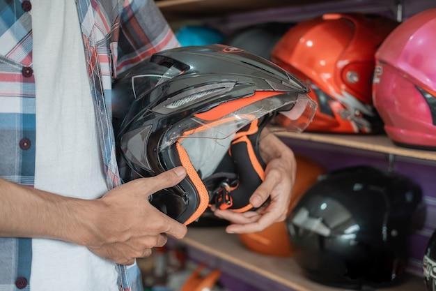 ヘルメットショップでヘルメットディスプレイラックの背景に対してヘルメットを持っている男の手