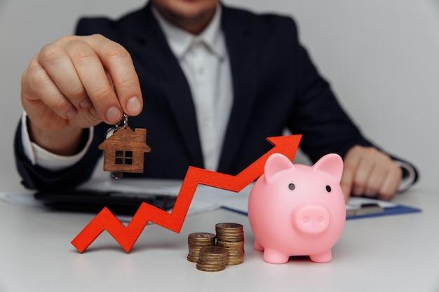 남자 손을 잡고 집 열쇠. 빨간색 화살표와 동전 돈의 스택입니다. 사업 투자 및 부동산 개념